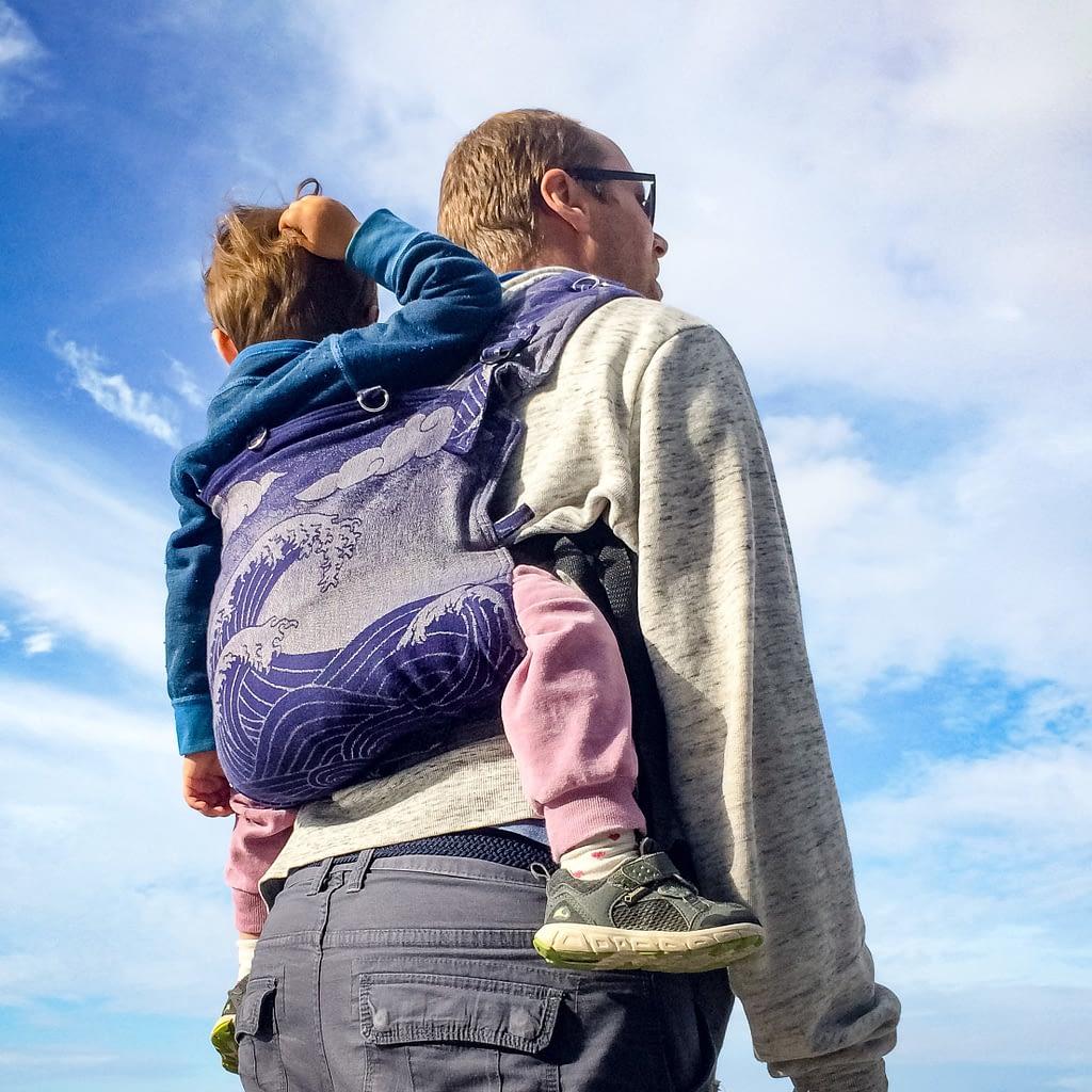 Mann bærer barn i sele på rygg